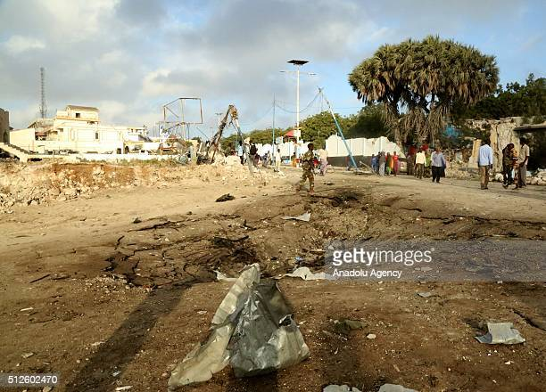 People inspect the area after fighters detonated a car bomb outside a hotel in the capital Mogadishu before storming the building on February 27 2016...