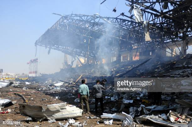 People inspect the area after Saudiled coalition's air strikes over EsSebin square of Sanaa Yemen on November 5 2017