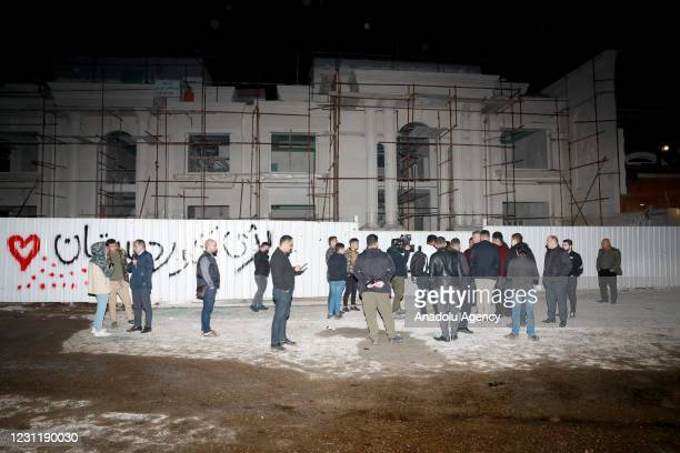 People inspect the area where one of the fired rockets was hit at Bahtiyari neighborhood on February 15, 2021 in Erbil, Iraq. According to the...