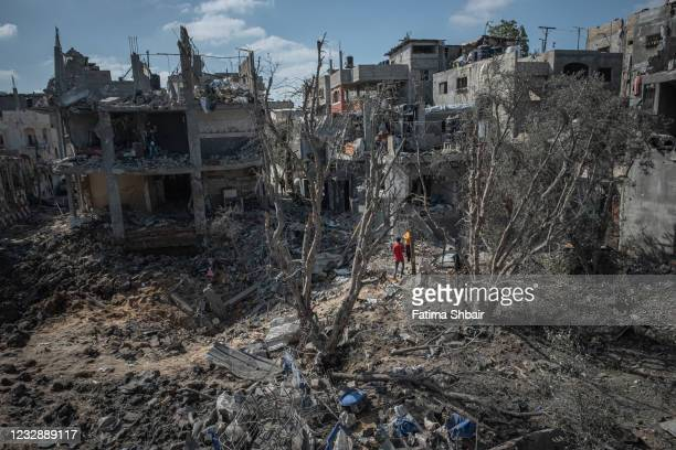 People inspect the damage done to Beit Hanoun after a night of Israeli raids on May 14, 2021 in Gaza City, Gaza. More than 100 people in Gaza and...