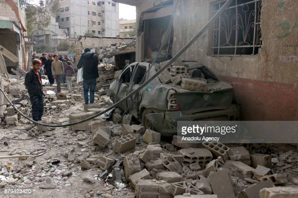 People inspect the debris of a building after Assad regime's warplane carried out airstrikes over residential areas of Mesraba district of the...