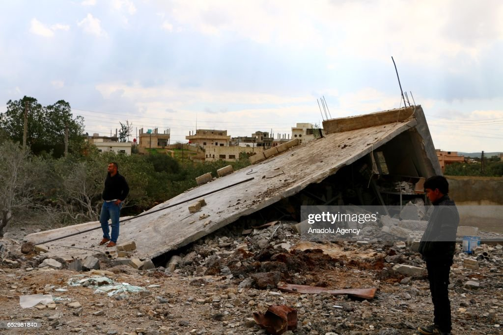 People inspect the debris of a building after warcrafts belonging to Assad Regime forces carried out airstrike in Umm al-Mayadeen district of Daraa, Syria on March 13, 2017.