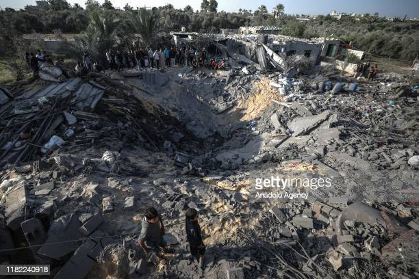 People inspect the debris of a building and huge holes after Israeli airstrikes hit the residential area of Khan Yunis, Gaza on November 14, 2019.