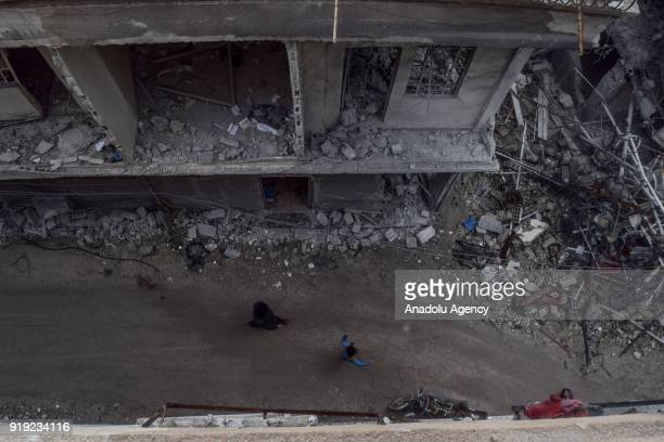 People inspect the debris of buildings after Assad Regime's airstrikes and ground attacks to Harasta town in the besieged Eastern Ghouta in Damascus...