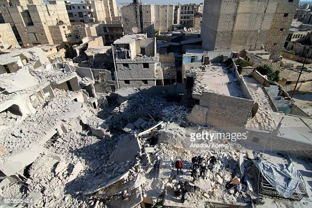 People inspect the debris of the collapsed buildings after the Assad Regime's and Russian forces' airstrikes over residential areas in Maadi...