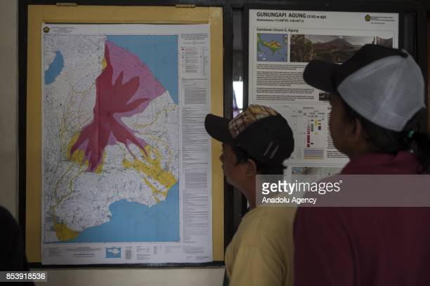 People inspect the information board containing the danger zones around Mount Agung in Bali Indonesia on September 26 2017 Indonesian authorities...