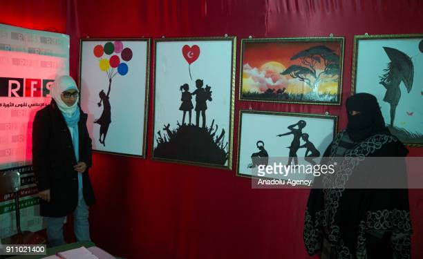 People inspect the paintings of Syrian painters Fatima Ahmed and Hikmet Ismael during an art exhibition which is on Syrian people's experience,...