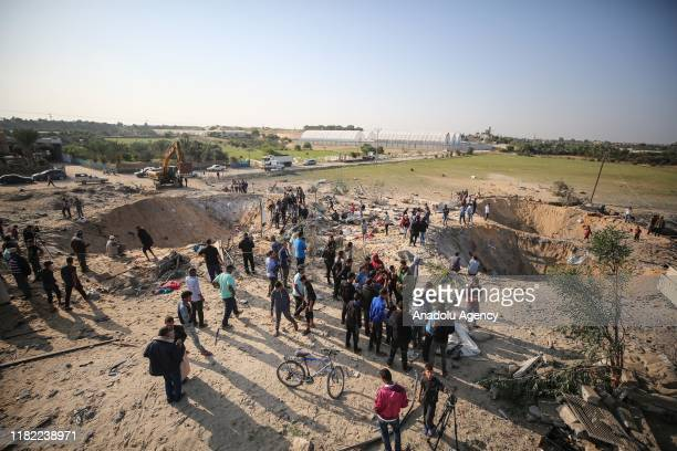 People inspect the site and huge holes after Israeli airstrikes hit the residential area of Deir al Balah, Gaza on November 14, 2019. Two days of...