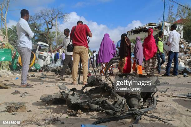 People inspect the site near the wreckage after bombladen vehicle attack by AlShabaab militants to a restaurant in Mogadishu Somalia on June 15 2017...