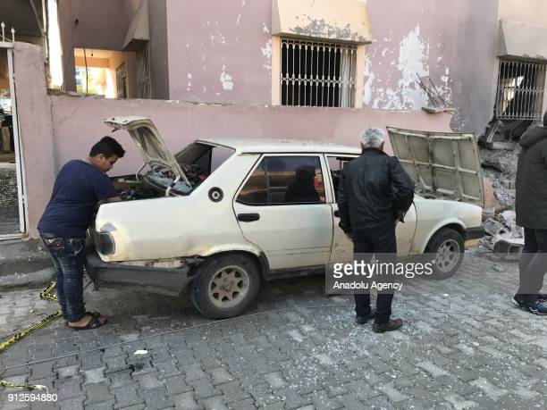 People inspect the site of a rocket attack by Syrianbased PYD/PKK terrorists on January 31 2018 in Reyhanli district of Hatay Turkey Turkey launched...