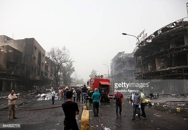 People inspect the streets after workplaces and houses were damaged in car bomb blast claimed by the terrorist organization DAESH in the Karrada...
