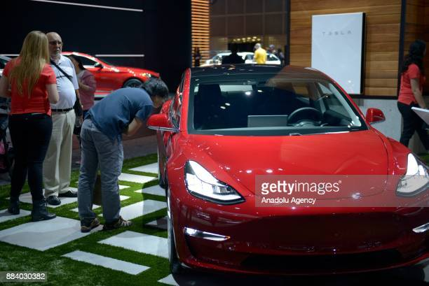 People inspect the Tesla Model 3 as it sits on display at the Los Angeles Auto Show in the Los Angeles Convention Center in Los Angeles California...