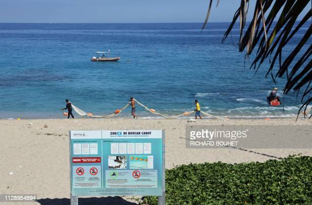 People install swimming enclosure nets to prevent shark attacks at the Boucan Canot beach on the Indian Ocean island of La Reunion on February 26...