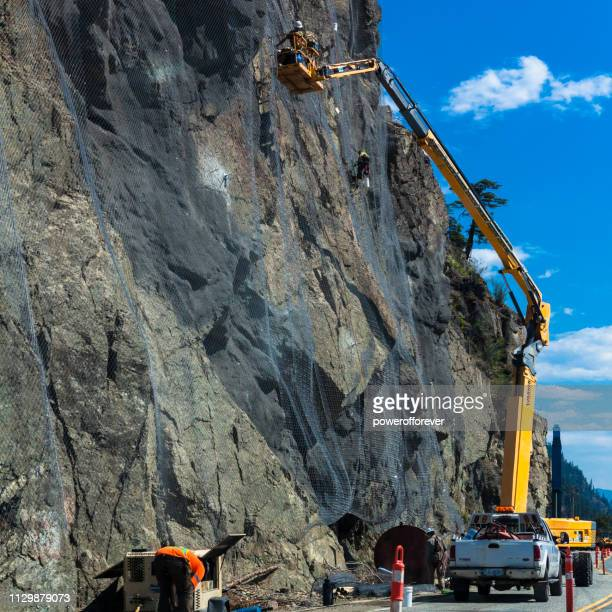 People Installing Landslide Debris Mitigation Fence in the Canadian Rocky Mountains of British Columbia, Canada
