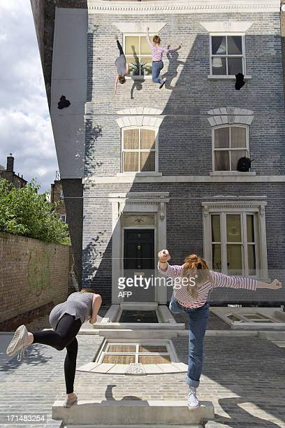 People interact with a largescale installation art piece by Argentinian artist Leandro Erlich entitled Dalston House in East London on June 25 2013 A...