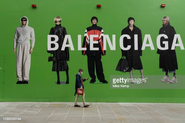 People interact with large scale action figures wearing fashionable clothing against a huge green hoarding which covers the Balenciaga store during a...