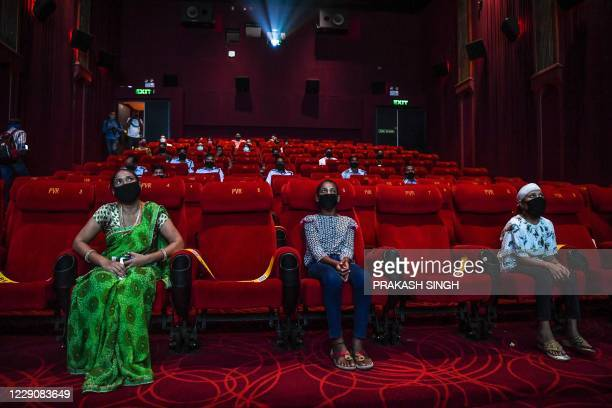TOPSHOT People invited as 'Covid19 warriors' and their families to a special screening watch Bollywood movie 'Tanhaji' in a cinema in New Delhi on...