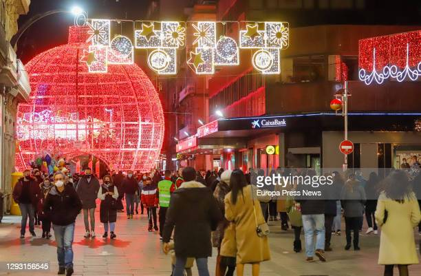 People is seen walking under the Christmas lights, on 25 December in Vigo, Galicia . Vigo is closed at the perimeter, but open between December 23rd...