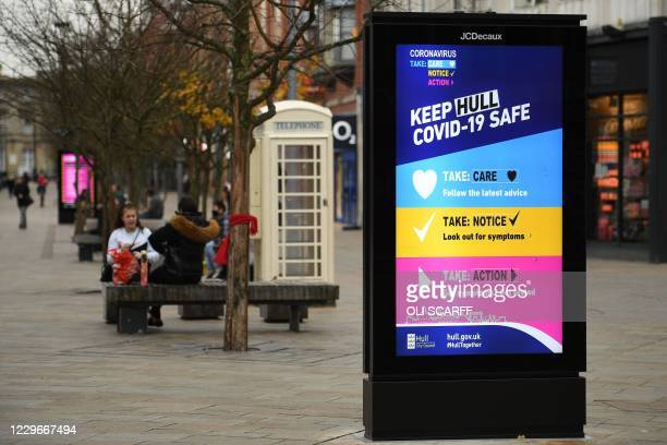 People ist near an electronic poster displaying COVID-19 information in Hull, in northern England on November 18 following a rise in the number of...