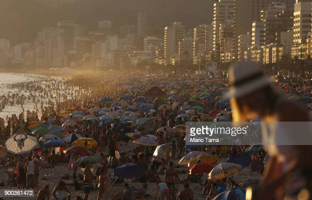 People jam Ipanema beach before the first sunset of 2018 on January 1 2018 in Rio de Janeiro Brazil Fireworks were launched earlier in Rio and cities...