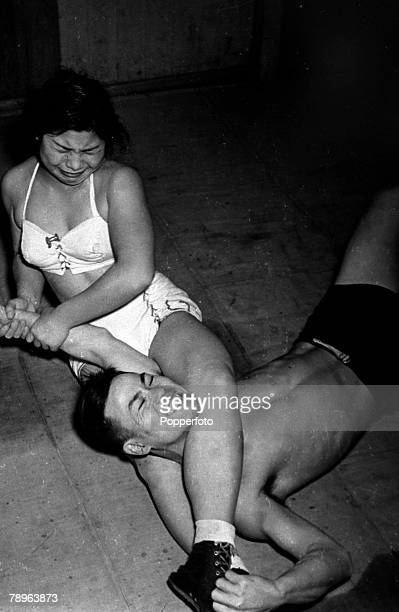circa 1960's A man and woman wrestling each other with the woman holding the man in a head lock