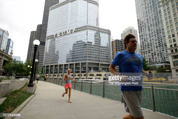 People jog along the Chicago River walk near Trump International Hotel Tower in Chicago Illinois Tuesday July 31 2018 Some individual investors who...