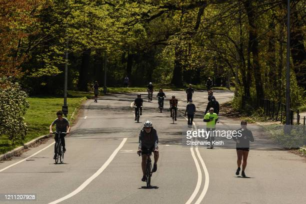 People jog and ride bicycles in Prospect Park on April 28, 2020 in the Brooklyn borough in New York City. New York City Parks Department has kept the...