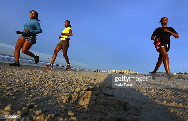 People jog at sunrise at Rockaway Beach on August 19 2012 in the Queens borough of New York City Over the last few years the Rockaways peninsula has...