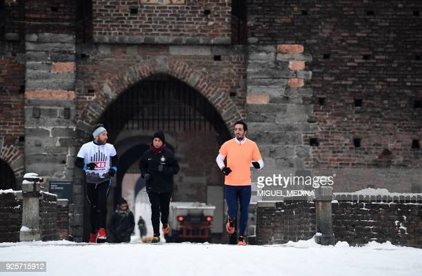 People jog in Sempione garden after a night of snowfall in Milan on March 1 2018 Fresh heavy snowfalls and icy blizzards were expected to lash Europe...