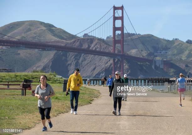 People jog near the Golden Gate Bridge amid the coronavirus outbreak on April 27, 2020 in San Francisco, California. The Coronavirus pandemic has...
