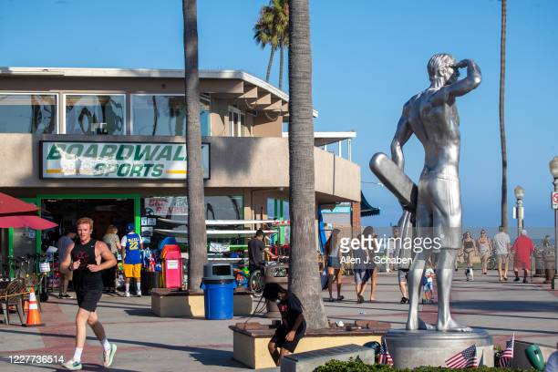 People jog, ride and skateboard on the sidewalk past businesses and the the Ben Carlson memorial statue near the pier on a summer day Monday, July...