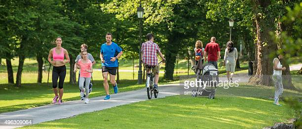 people jogging in park - public park stock photos and pictures
