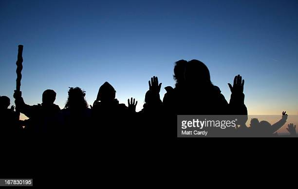 People join in a Beltane dawn celebration service in front of St Michael's Tower on Glastonbury Tor on May 1 2013 in Glastonbury England Although...
