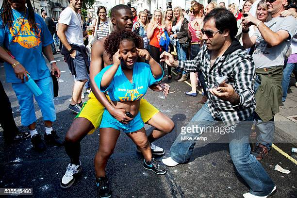 People joking and laughing and dancing along with a woman dwarf at the Notting Hill Carnival in West London The Notting Hill Carnival is an annual...