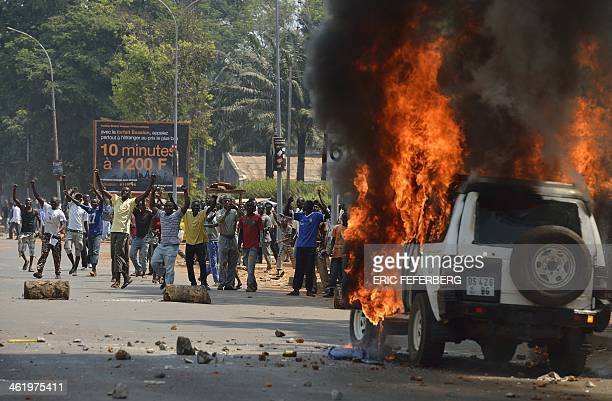 People jubilate after they throw stones and burned a car transporting two children of an exSeleka colonel at the 'UN crossroad'' on January 12 2014...
