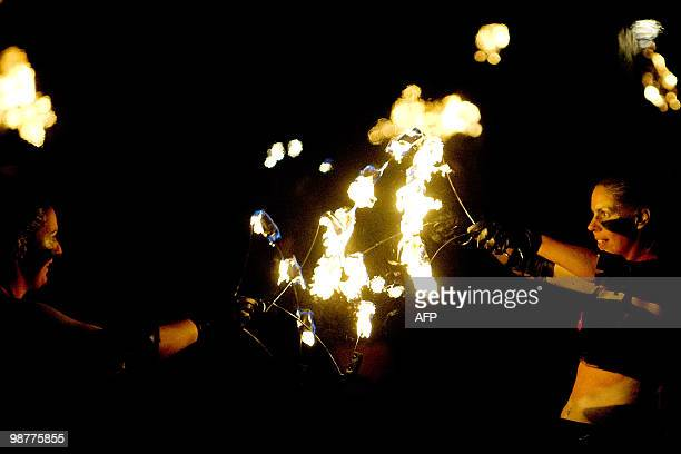 People juggle with fire during the Beltane Fire Festival in Edinburgh on April 30 2010 The event which celebrates an ancient Celtic festival is a...