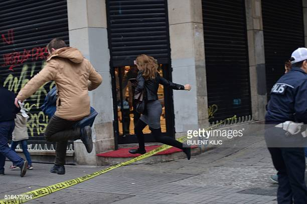 People jump a police line to flee the scene of an explosion on the pedestrian Istiklal avenue in Istanbul on March 19 2016 Two people including the...