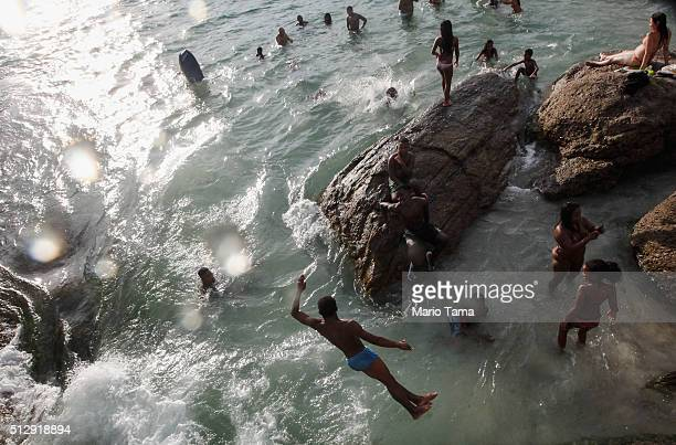 People jump and swim along Arpoador rock a popular tourist destination on February 28 2016 in Rio de Janeiro Brazil The Zika virus outbreak which may...