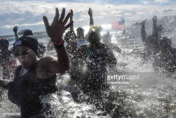 People jump into the Atlantic Ocean during the annual Polar Bear Plunge on New Year's Day in Coney Island on January 1 2019 in the Brooklyn borough...