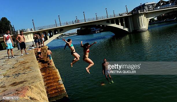 People jump into the Guadalquivir river during a heatwave in Sevilla on June 28 2015 A powerful heatwave was forecast to sweep across Europe's...