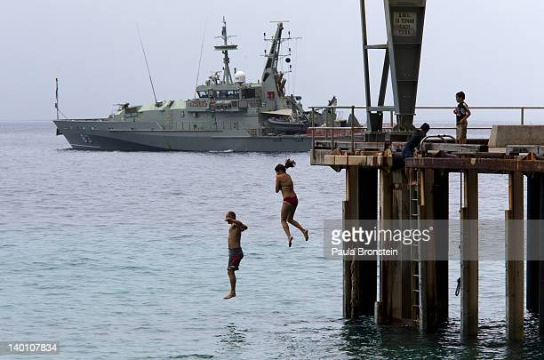 People jump into the ocean near to an Australian Navy boat docked at the Flying Fish Cove February 28 2012 on Christmas Island Australia One man has...