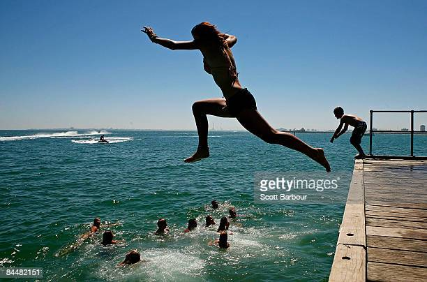 People jump of the pier at St Kilda beach as a heatwave hits Melbourne on January 27 2009 in Melbourne Australia The temperature today is estimated...