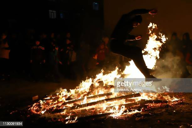 People jump over the bonfire as part of the Newroz celebrations marking the arrival of spring in Baku Azerbaijan on March 12 2019