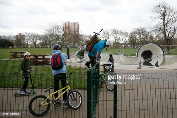 People jump the fence at the Victoria Park skatepark on March 6, 2021 in London, England. Londoners are enjoying bright weather as end of lockdown...