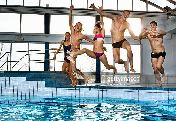 People jumping into swimming pool