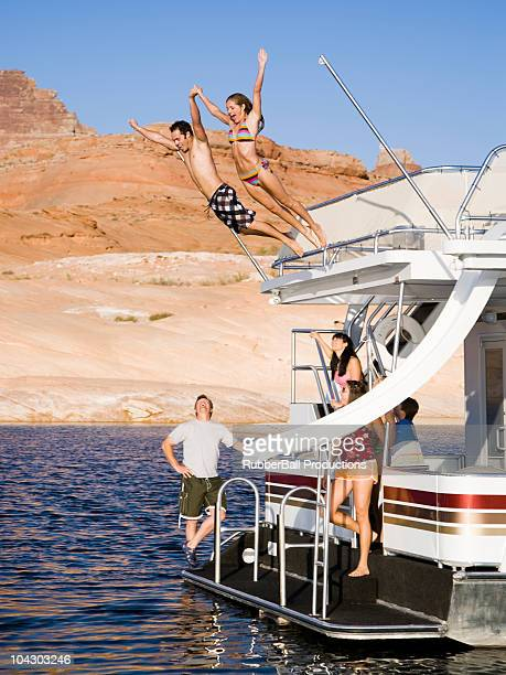 people jumping off a houseboat