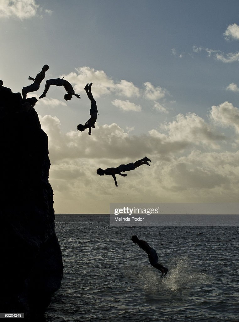 People jumping off a rock at Waimea Bay : Stock Photo