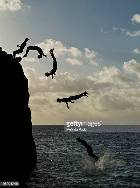 people jumping off a rock at waimea bay - waimea bay stock photos and pictures