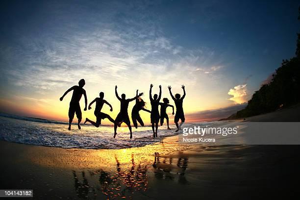people jumping on beach at sunset in costa rica - península de nicoya fotografías e imágenes de stock