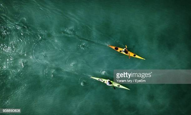 people kayaking in sea - kajak stock-fotos und bilder